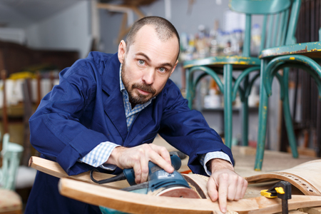 Confident workman using tools while working at repair shop, renovating vintage chair