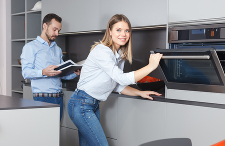 Young family couple looking at exhibition model of kitchen in salon while designing home interior Stock Photo