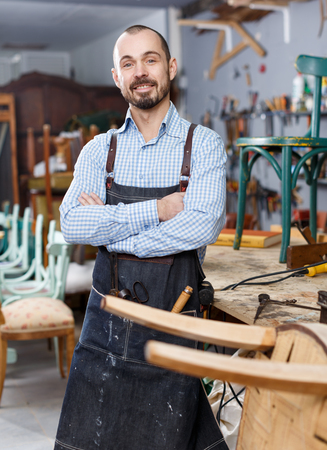 Cheerful craftsman in working clothes posing in furniture restoration studio