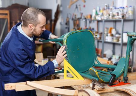 Professional young man carpenter repairing antique furniture in workshop Standard-Bild - 114514345