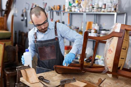 Focused craftsman engaged in retro furniture repair covering with oil vintage armchair in modern workshop
