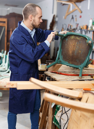 Concentrated craftsman using carpentry tools for restoration old armchair in workshop Banque d'images