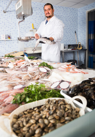 Seller 30-39 years old in white cover-slut holding fish in his hand Stock Photo