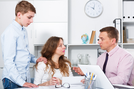 Middle-aged mother and son visiting consultation with school headmaster