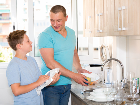 Man with his son are washing dishes on the kitchen at the home.