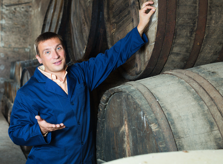 Smiling man in robe checking ageing barrel process of wine