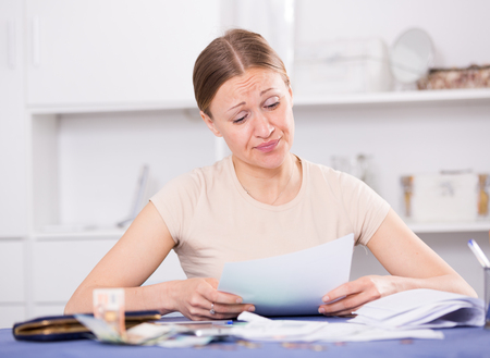 Young woman sitting at home worried about debts on bills
