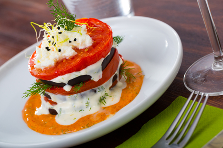 Healthy eating. Stack of fried eggplant with tomatoes, soft cheese and piquant sauce Stock Photo