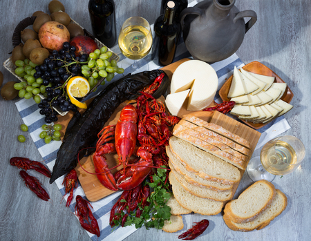 Top view of smoked sturgeon and boiled lobster with crayfishes, fruits and white wine on wooden table