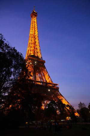 View of majestic illuminated Eiffel Tower in Paris at twilight, France