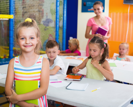 Cheerful junior girl standing with textbook in elementary school class indoors