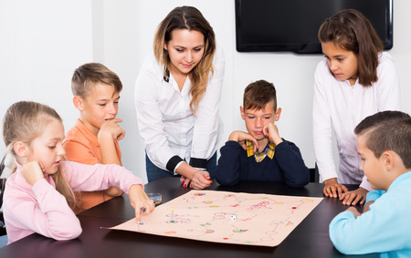 Happy kids sitting at table with board game in classroom