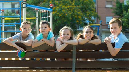 Glad  children sitting on a bench at the playground 免版税图像 - 114637310
