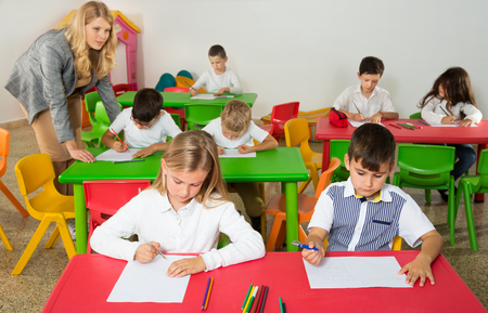 Group of school kids with pens and notebooks studying in a classroom with teacher