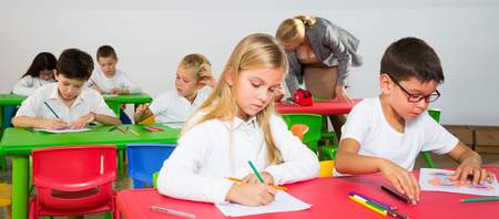 Boy and girl pupils of elementary school sitting at desk and teacher helping children on background
