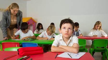 Porträt eines gelangweilten Schülers, der mit Klassenkameraden und Lehrer im Klassenzimmer sitzt