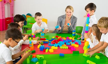 Cute schoolchildren creating constructions from toy blocks with teacher in classroom 免版税图像