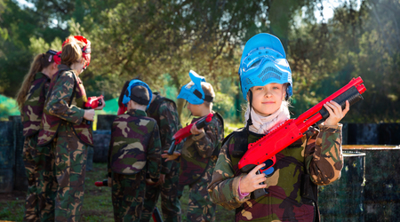 Happy cheerful  teen girl wearing uniform and holding gun ready for playing with friends on paintball outdoor