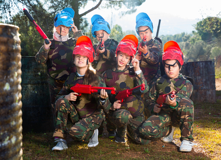 Friendly cheerful  smiling group of children paintball players in camouflage posing with guns on paintball playing field outdoors Фото со стока