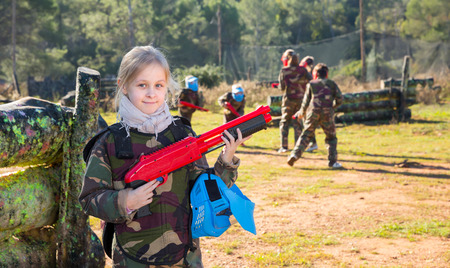 Portrait of joyful tween girl paintball player with marker gun ready for game outdoors Фото со стока