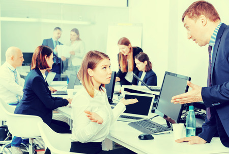 Outraged angry  manager expressing dissatisfaction with work of frustrated young pleasant woman in modern office Archivio Fotografico