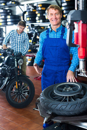 Attentive positive mechanic man standing with motorcycle wheel in shop