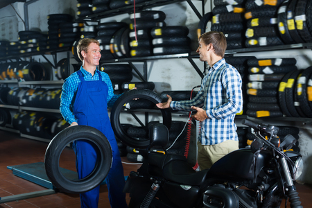 Professional positive mature mechanic taking to customer in shop Stock Photo