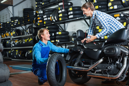 Portrait of diligent positive mechanic and smiling friendly customer chatting about motorbike tires at service point Stock Photo