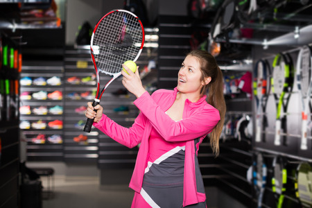 Smiling woman is testing new rocket and ball for tennis in the store. 版權商用圖片