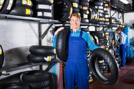 Mature attentive mechanic holding new tyre for motorcycle in workshop