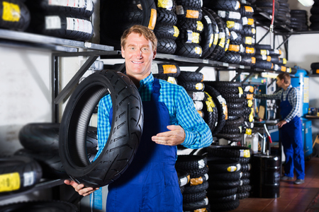 Positive working man standing with new auto tires for in hands in shop Stock Photo