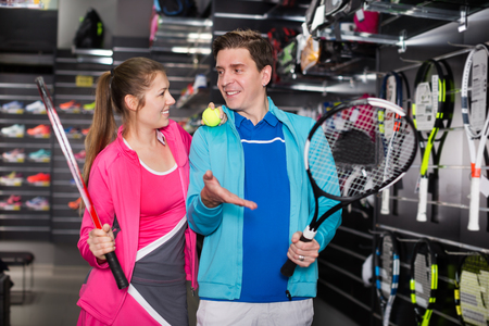 Tennis couple in sportwear is looking on modern rocket and ball for tennis in a store. Focus on man Imagens