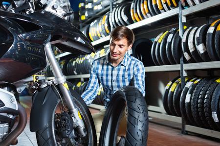 Portrait of glad smiling customer choosing new motorbike in workshop Imagens