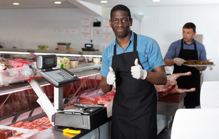 Portrait of satisfied African American male professional butcher in butcher shop