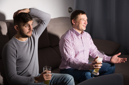 Two friends watching matchup on tv together, but supporting different teams
