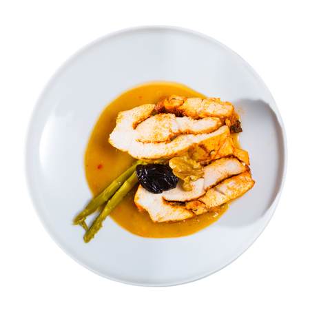 Top view of spicy baked turkey breast served in mango sauce with prune, walnuts and pickled asparagus. Isolated over white background