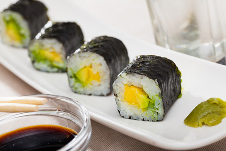 Appetizing Maki with avocado served on plate with soy sauce