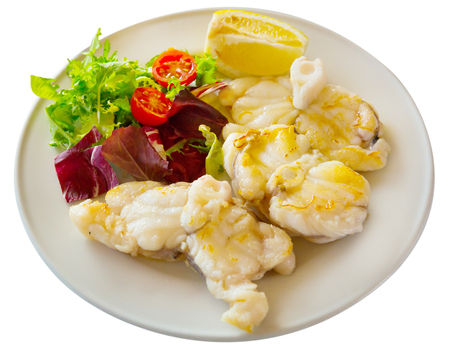 Healthy dinner, baked white fish steak with lemon and greens. Isolated over white background 写真素材