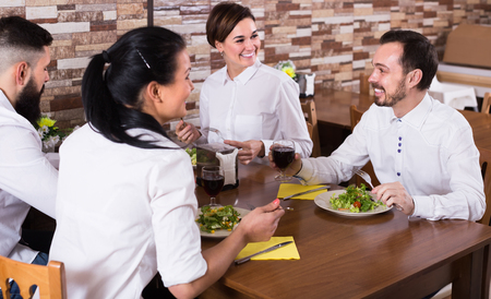 group of young friends eating at restaurant table and chatting Stockfoto