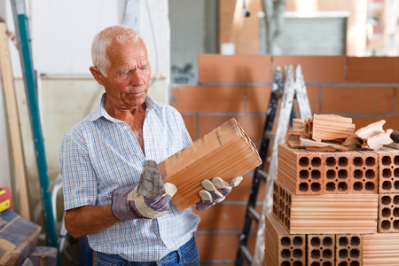 Confident senior man working with red brick on overhauls of his house