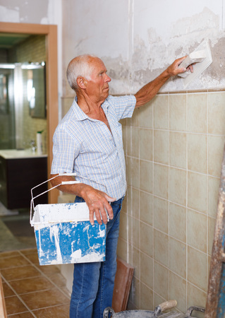 Old construction worker wearing casual clothing with plastering tools renovating walls of house