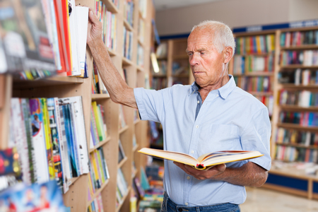 Senior male interested in books looking for necessary literature on shelves of bookstore