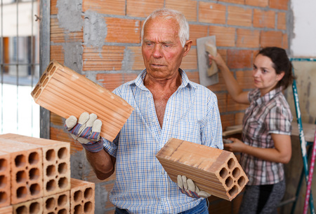 Skillful older man with young woman installing brick wall in building under construction