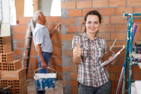 Heureuse jeune femme debout avec du papier à la main pendant les travaux de rénovation dans sa maison