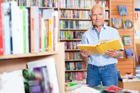 Focused efficient glad  positive elderly man looking for information in books in bookstore