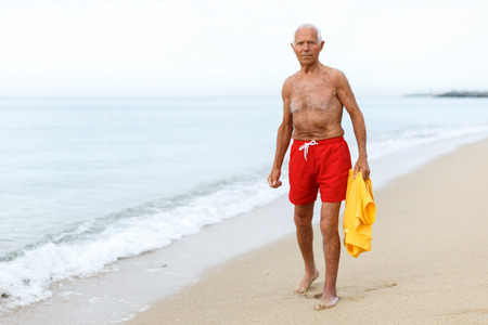 Nice elderly man in beachwear resting near ocean Stock Photo
