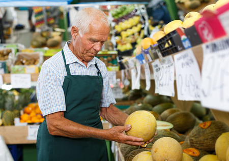 Elderly salesman of greengrocery store arranging fruits and vegetables on shelves