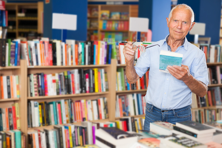 Modern mature man looking for books to read in his spare time in library