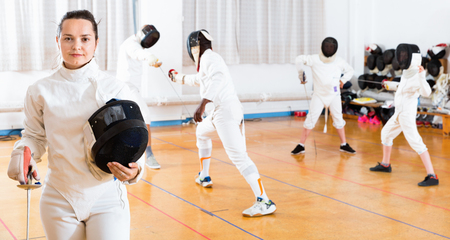Portrait of smiling sporty cheerful positive glad woman with foil at fencing workout Stock Photo