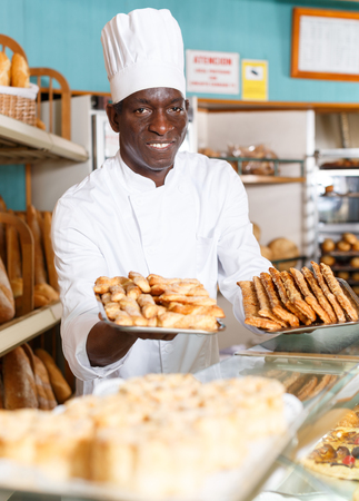 Happy African American worker of bakery in white uniform recommending fresh baked goods for sale
